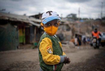 一个小男孩戴着口罩走过肯尼亚内罗毕的一个非正式定居点。