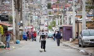 A man kicks a soccer ball up the street during lockdown in Alexandra Township, Johannesburg.