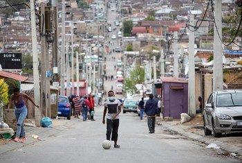 Un homme tape dans un ballon de football dans la rue pendant le confinement dans le canton d'Alexandra, Johannesburg, le 3 avril 2020.