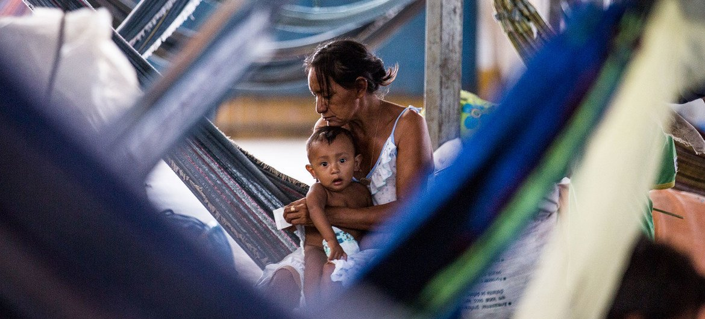 Una madre cuida de su bebé dentro de un gimnasio que se ha convertido en un asentamiento de refugiados en Pintolandia, en el Estado brasileño de Roraima, fronterizo con Venezuela.