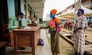 尼日利亚拉各斯,两名妇女在保持社交距离的情况下领取粮食署提供的食品换购券。