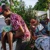 8月14日海地发生地震后,一名男子在一家医院等待治疗时被移到一张临时床上。