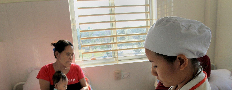 Una mujer y su hijo en la cama de un hospital en Camboya mientras una enfermera revisa el historial médico.