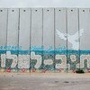 A mural on a wall in Netiv HaAsara, Israel, that faces the Gaza border and reads Path to Peace in Hebrew, Arabic, and English.