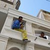 अलबानिया के तिराना में कामगार एक इमारत की मरम्मत के काम में जुटे हैं.