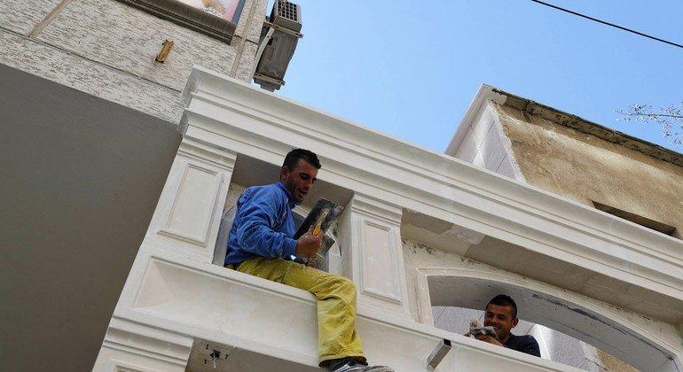 Dos hombres trabajan en la renovación de un edificio en  la ciudad de Tirana, la capital de Albania.