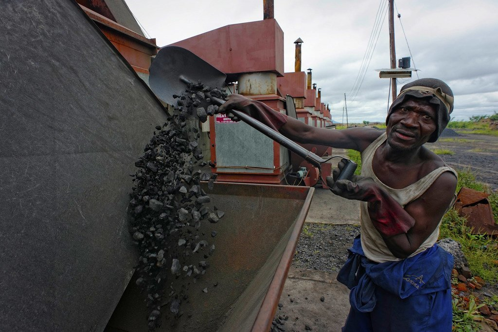 Au Malawi, un ouvrier remplit une chaudière de charbon dans une entreprise de production de tabac.