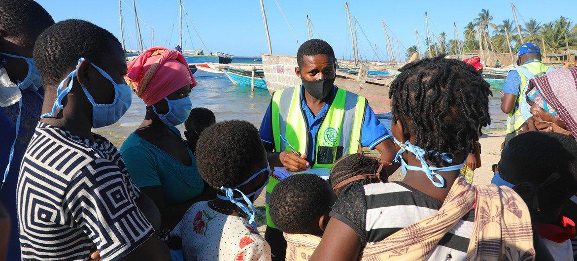 Em Moçambique, pessoas deslocadas internamente que fogem da insegurança em Cabo Delgado chegam de barco na praia de Paquitequete, em Pemba.