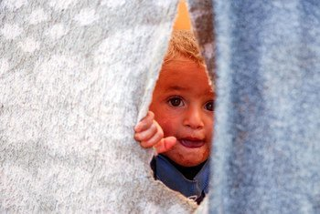 A Syrian child peeks out of a temporary shelter in an informal settlement in Killi, near the border with Turkey. (2019)