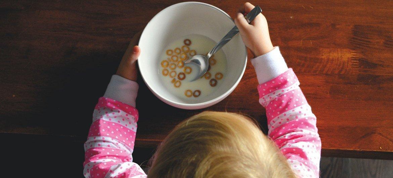 Una niña desayunando sentada en una mesa.