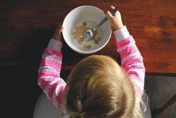एक छोटी बच्ची मेज़ पर बैठकर नाश्ता करते हुए.