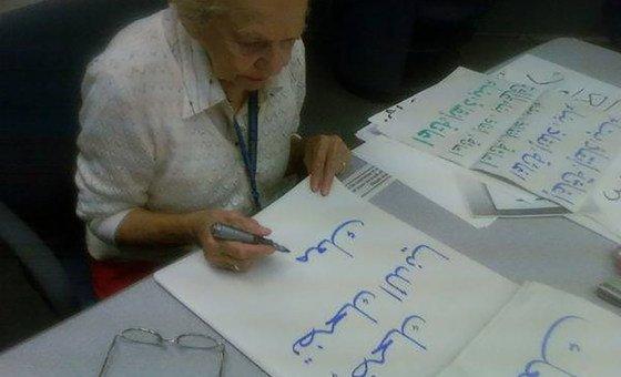 """طالبة في الأمم المتحدة تتعلم الخط العربي، وتكتب: """"إضحك، تضحك الدنيا معك""""."""