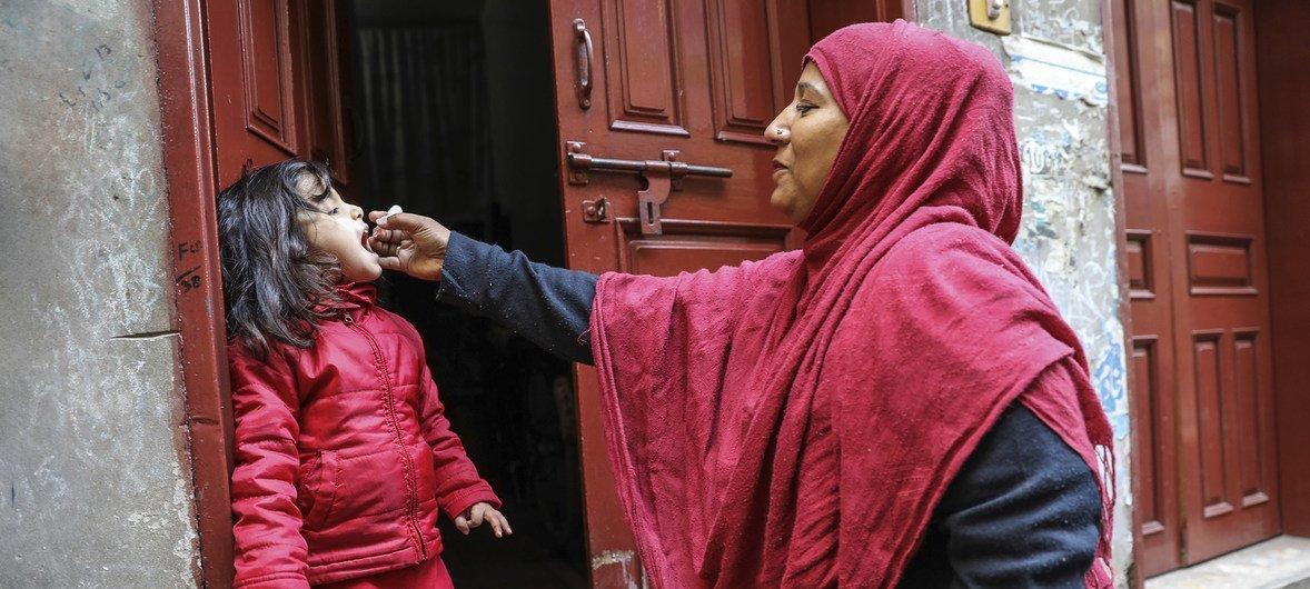 Uma profissional de saúde vacina uma menina de 4 anos contra a poliomielite na porta de sua casa, na província de Lahore Punjab, no Paquistão.