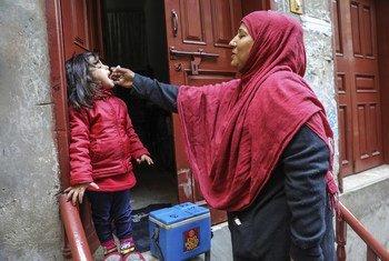 Un agent de santé vaccine une fillette de 4 ans contre la polio à la porte de sa maison dans la ville de Lahore, dans la province du Punjab, au Pakistan.