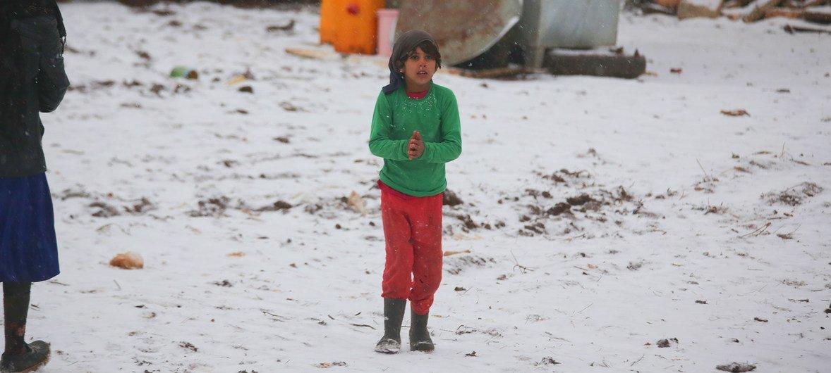 Un niño camina sobre la nieve en un asentamiento informal acabado de construir. El enclave recibe a familias recientemente desplazadas de las provincias de Idlib y Alepo, en el noroeste de Siria.