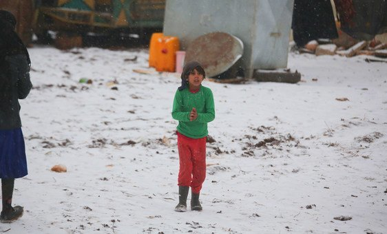 Uma criança caminha na neve em um assentamento informal que continua recebendo famílias recém-deslocadas do sul de Idlib e das províncias rurais de Alepo, no noroeste da Síria.