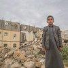 Un jeune garçon se tient devant des bâtiments endommagés à Saada, au Yémen.