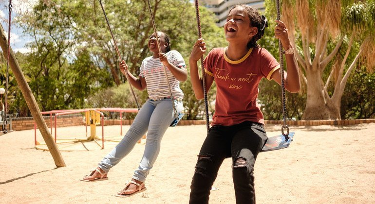Two young girls play on swings in a playground in Namibia.