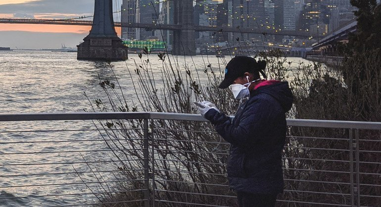 A woman wearing a protective mask and gloves checks her phone while walking along the East River in New York.