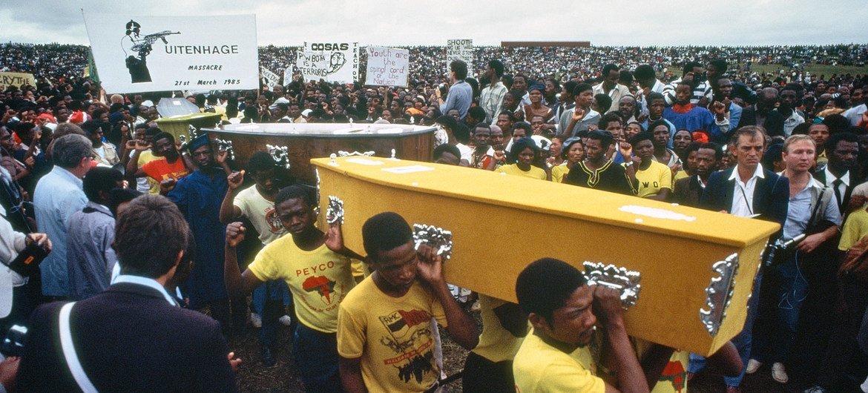 वर्ष 1985 में नस्लीय भेदभाव के उन्मूलन के अन्तरराष्ट्रीय दिवस पर दक्षिण अफ़्रीकी पुलिस द्वारा मारे गए लोगों के ताबूतों को ले जा रहे शोकाकुल लोग.