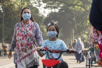 Una niña y su madre usan mascarillas para moverse por las calles de Bangladesh, una escena cotidiana de la pandemia de COVID-19 que empezó a principios de 2020.