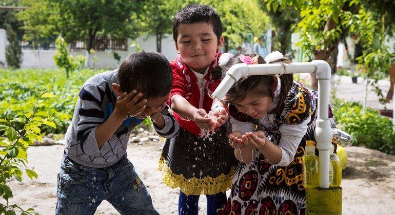 أطفال يغسلون أيديهم من صنبورة مياه في أوزباكستان، 2018.