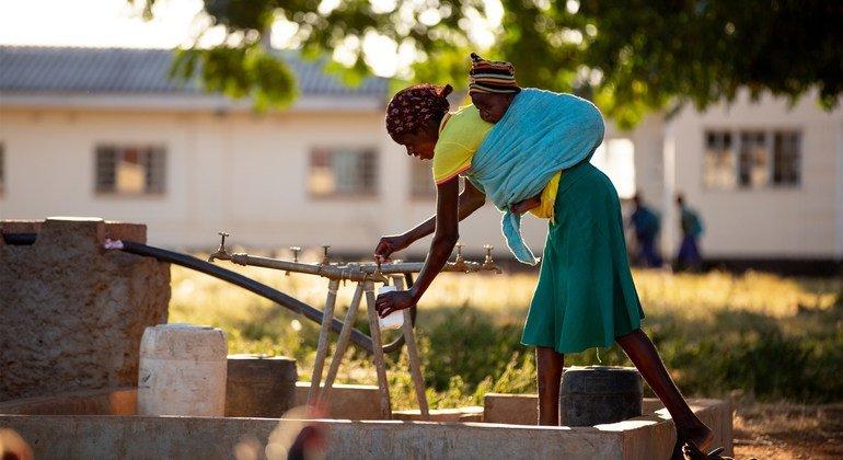 أمّ تجمع المياه قرب أحد المستشفيات في زمبابوي (6 حزيران/يونيو 2018).