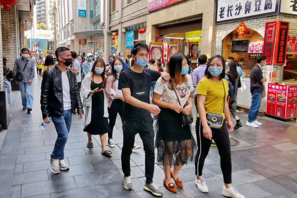 Des habitants de Shenzhen, en Chine, sont dans la rue portant des masques à cause de la pandémie de coronavirus.