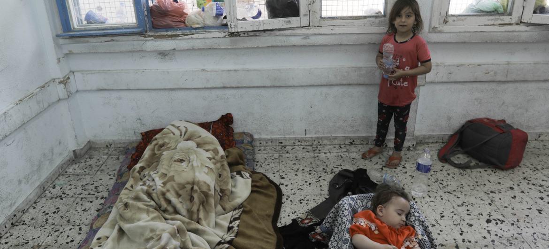 Mtoto akiangalia mtoto mwinzie akiwa amelala darasani kwenye shule inayosimamiwa na UNRWA Gaza