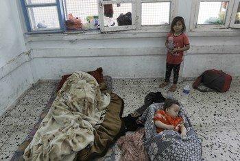 طفلة صغيرة تحرس إخوتها الصغار النائمين في فصل دراسي بمدرسة صلاح الدين التابعة للأونروا في غزة.