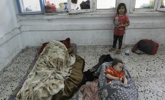 A young child watches over her toddler siblings sleeping in a classroom of UNRWA Salah Eddin School in Gaza.