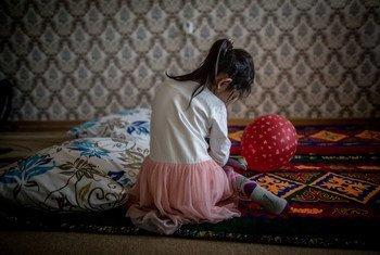 فتاة في الخامسة من عمرها تجلس في منزل أسرتها في كزاخستان، حيث تقوم اليونيسف بزيارات منزلي للقضاء على العنف المنزلي.