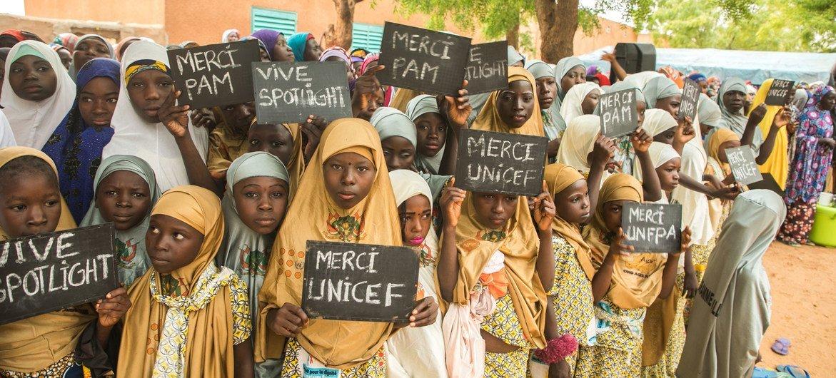 Des jeunes filles du village de Danja au Niger tiennent des pancartes en appui à l'initiative Spotlight.