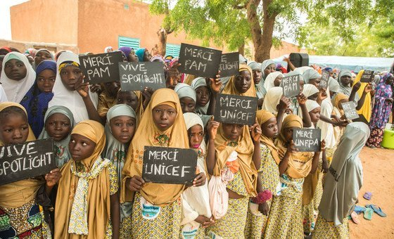 Young girls in the village of Danja in Niger hold signs in support of the Spotlight Initiative.