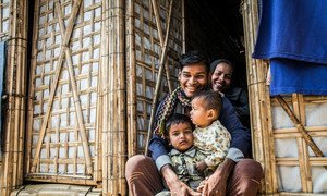 A Rohingya refugee family sit in the doorway of their new monsoon-ready shelter in Cox's Bazar, Bangladesh.
