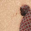 A 10-year-old girl, who was a victim of abuse, stands in front of her house in Maradi, Niger.
