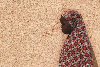 一名遭受虐待的10岁尼日尔女孩站在家门口。