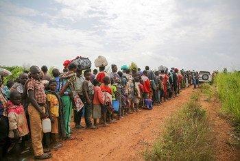 Solicitantes de asilo congoleños hacen cola para someterse a un control de seguridad y sanitario en Zombo, cerca de la frontera entre Uganda y la República Democrática del Congo.