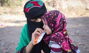 أم تطعم ابنتها بالبسكويت المغذي الذي حصلت عليه من مركز صحي متنقل في اليمن.