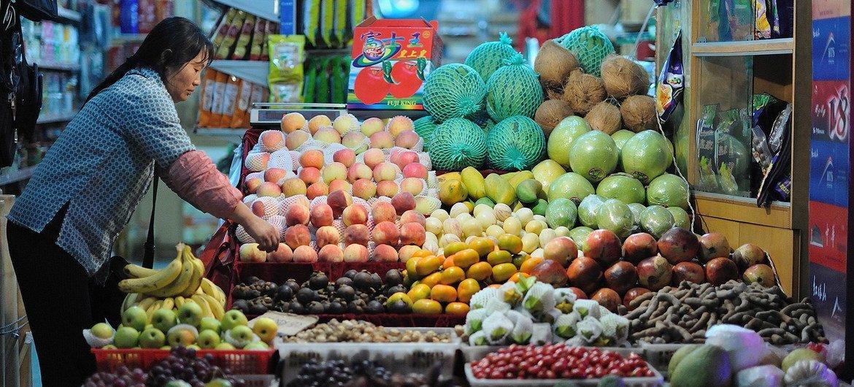云南昆明的一位女摊主正在整理她的水果摊。