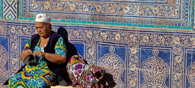 """乌兹别克斯坦希瓦古城著名的""""石头宫""""外,一名女性正在编织。"""