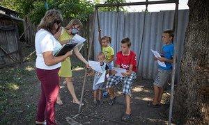 一名社会工作者(左)和一名心理学家(左二)在乌克兰东部探亲期间给当地孩子们发放配色图册和练习册。