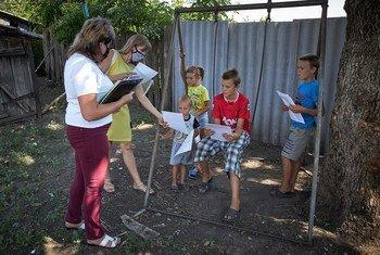 أخصائية اجتماعية (يسار) وخبيرة سيكولوجية (أقصى اليسار) تقدمان كراسات ألوان وكتبا للأطفال في شرقي أوكرانيا، خلال زيارة منزلية لأحد الأسر.