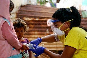 Albanis Oliva, Coordinatrice d'une ONG locale au Venezuela, aide les jeunes enfants à se laver les mains pendant la pandémie de COVID-19.