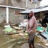 हेती में 7.2 की तीव्रता वाले भूकम्प में क्षतिग्रस्त हुई कुछ इमारतों के पास मौजूद कुछ लोग.हेती में, भूकम्प के दो दिन बाद ही एक शक्तिशाली तूफ़ान भी आया था.