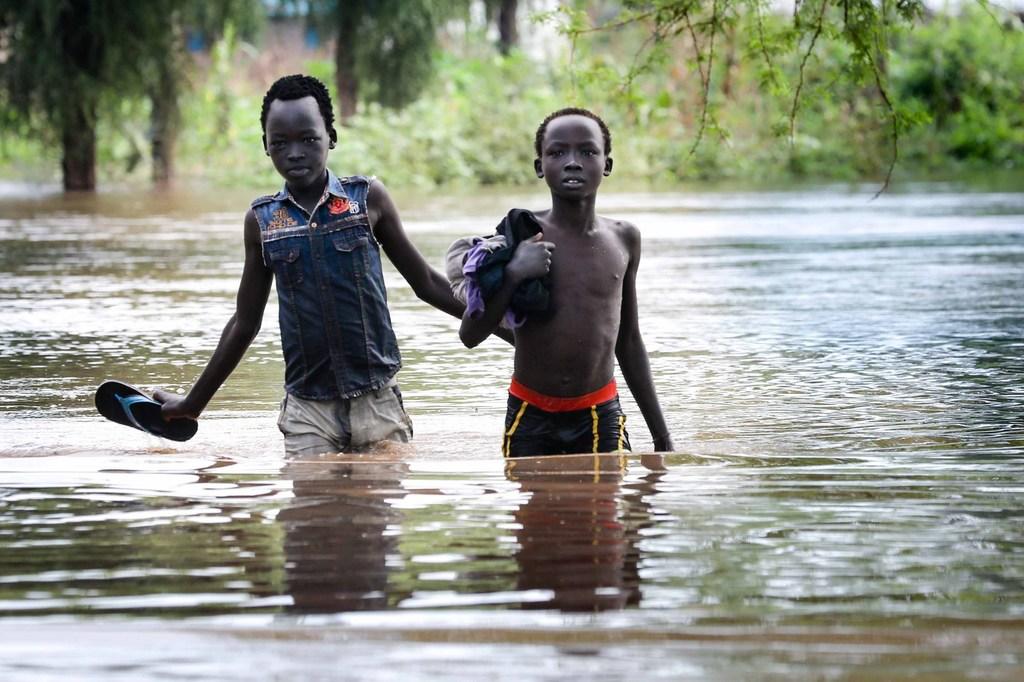 在埃塞俄比亚马班县的难民营中,两个男孩在没过膝盖的洪水中行走。