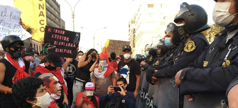 Un grupo de manifestantes se arrollidan ante la policía en las calles de Lima,la capital peruana.