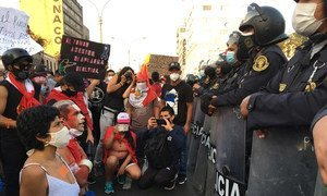 A group of protesters kneeling in front of police officers during demonstrations in Lima, Peru, in November 2020.