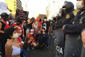 Un groupe de manifestants agenouillés devant la police.