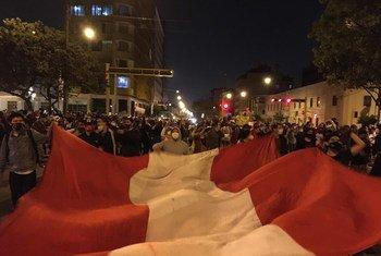 Manifestantes despliegan una bandera de Perú.